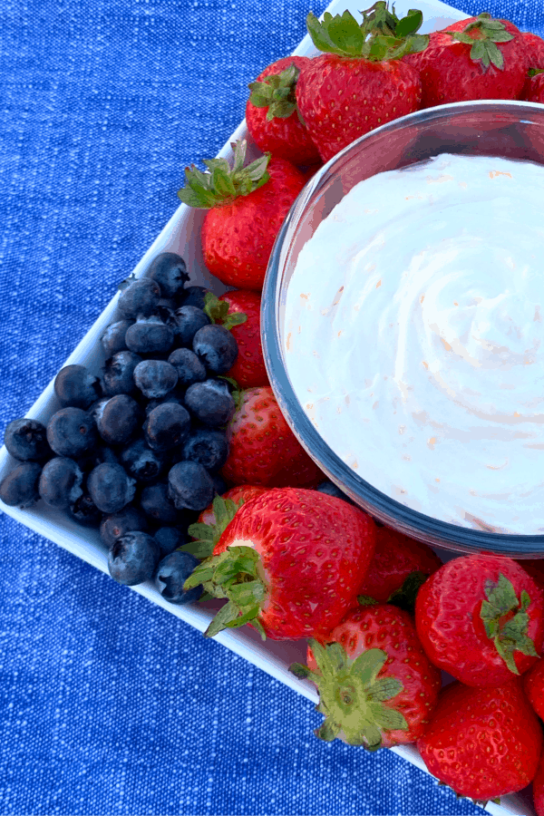 Sweet cream cheese fruit dip in small bowl on square white plate with strawberries and blueberries on blue napkin
