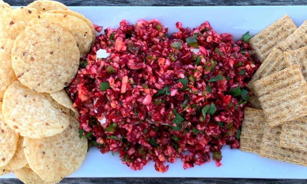 Platter of cranberry jalapeno and cilantro salsa with chips and crackers for dipping