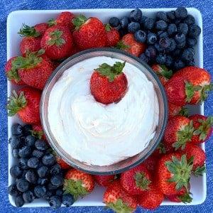 Cheesecake dip for fruit in center of fruit platter on blue napkin