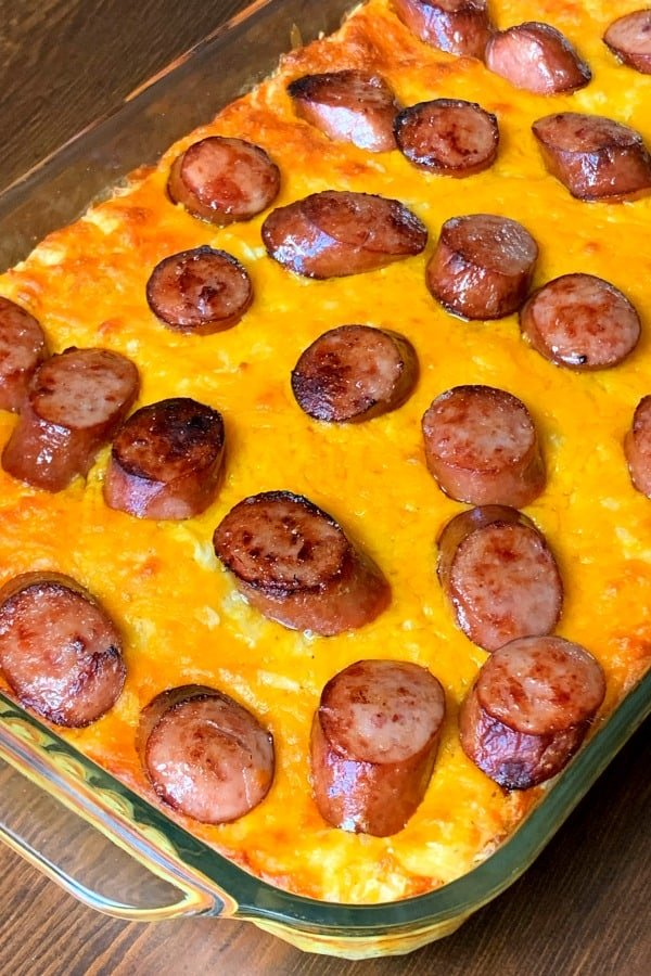 Cheesy potato casserole covered with sausage pieces