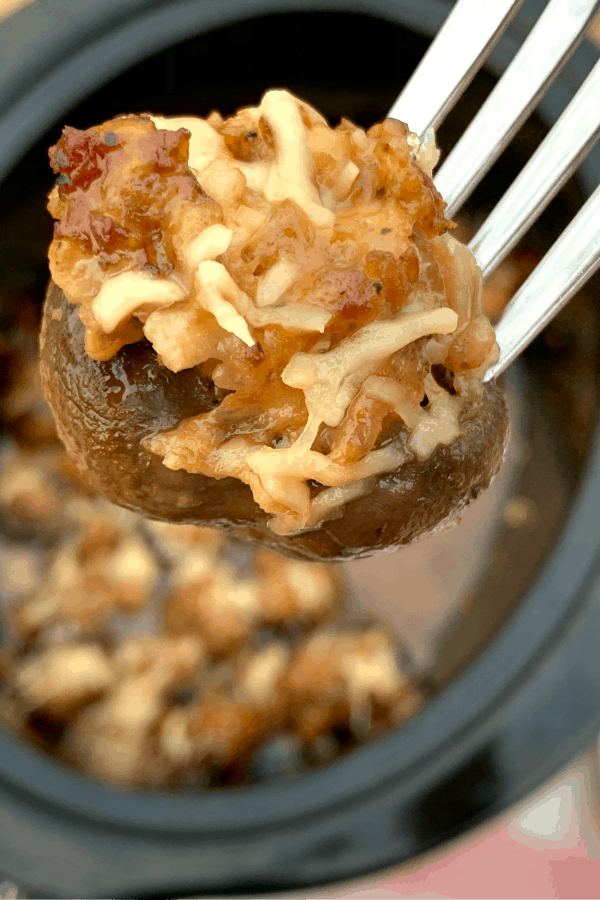 stuffed mushroom on a fork over a crock pot
