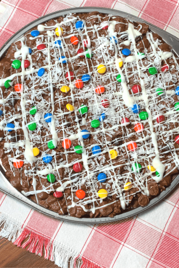 M&M candy pizza with other chocolate on a red plaid napkin