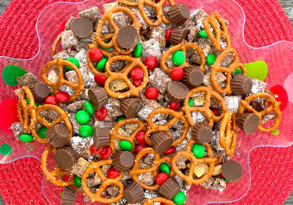 Reindeer chow in a decorative Christmas serving bowl is Confectioners sugar covered chex cereal, mini reeses cups, M&Ms and pretzels