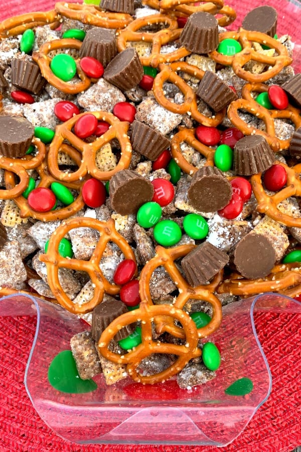 Reindeer food made with chex mix, pretzels and chocolate candy in a decorative Christmas serving bowl