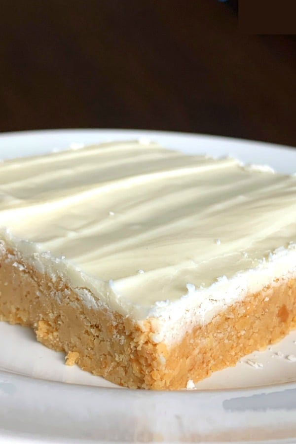 peanut butter candy like bar covered in a layer of white chocolate on a white plate