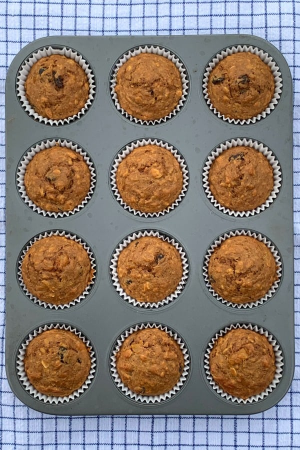 Muffin pan full of the best all bran muffins on blue plaid cloth