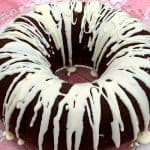 Chocolate spice bundt cake with white icing on a glass tray on a red napkin