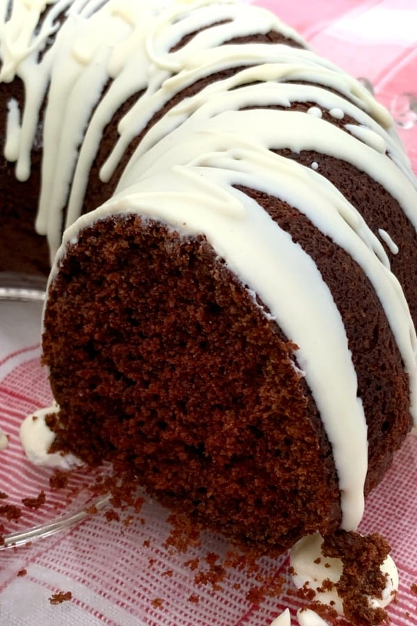 Chunk of chocolate spice bundt cake with moist crumbles and covered in icing