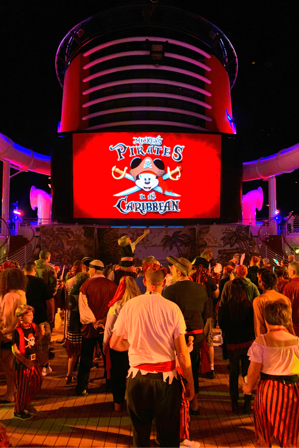 Mickey's Pirate Night with people dressed like pirates on the pool deck of a Disney Cruise