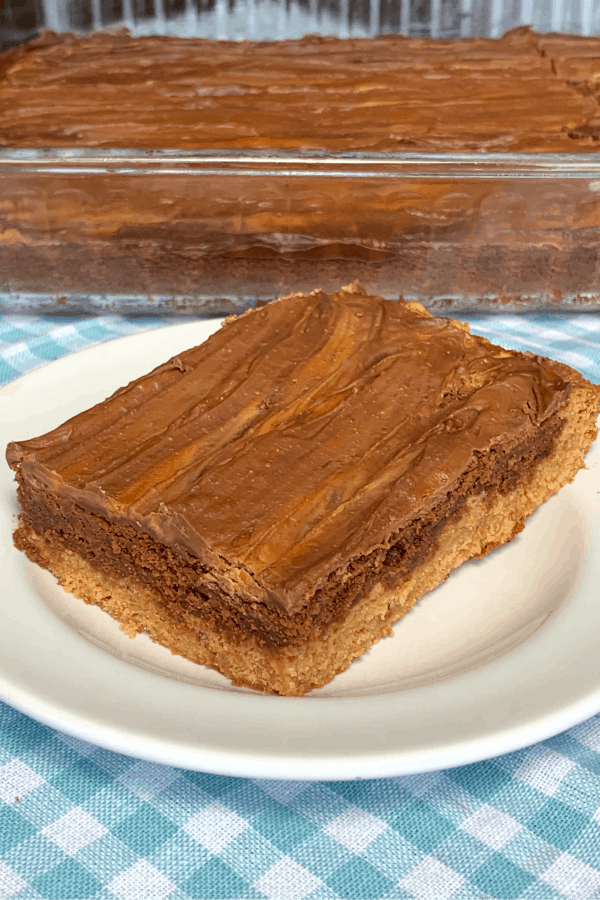 Big Chocolate and butterscotch layered brownie on a white plate on teal plaid napkin by pan of brownies
