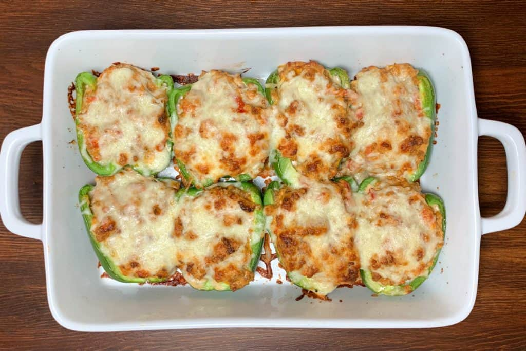 White baking dish of green stuffed peppers with Italian sausage and cheese