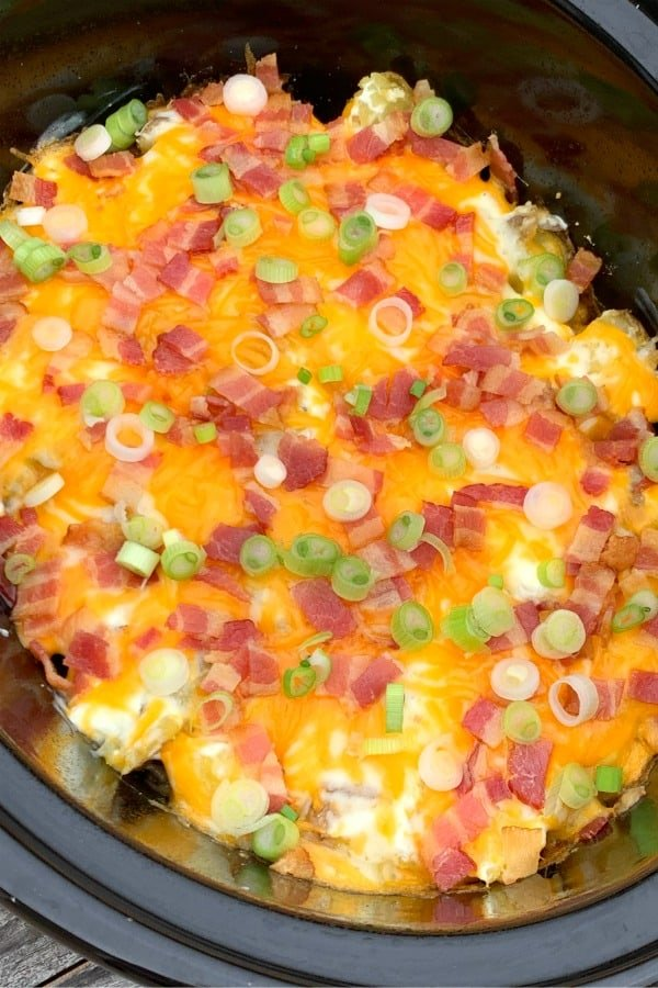 Crock pot of twice baked potato casserole topped with a thick layer of cheese, bacon and green onions