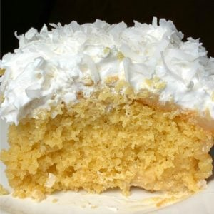 Up close piece of tropical cake with pineapple, coconut, sweetened condensed milk, cool whip and cream of coconut