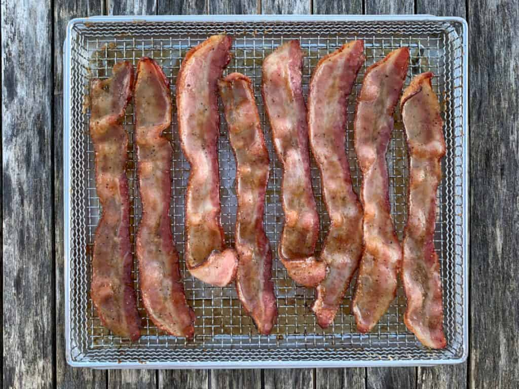 8 strips of candied bacon in air fryer basket on wood background
