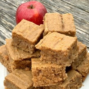 Applesauce breakfast bars on wood next to apple