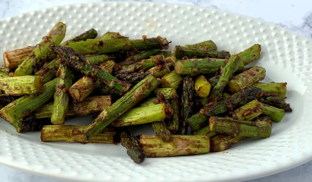 White dish of air fried asparagus with oil, garlic ginger & soy sauce