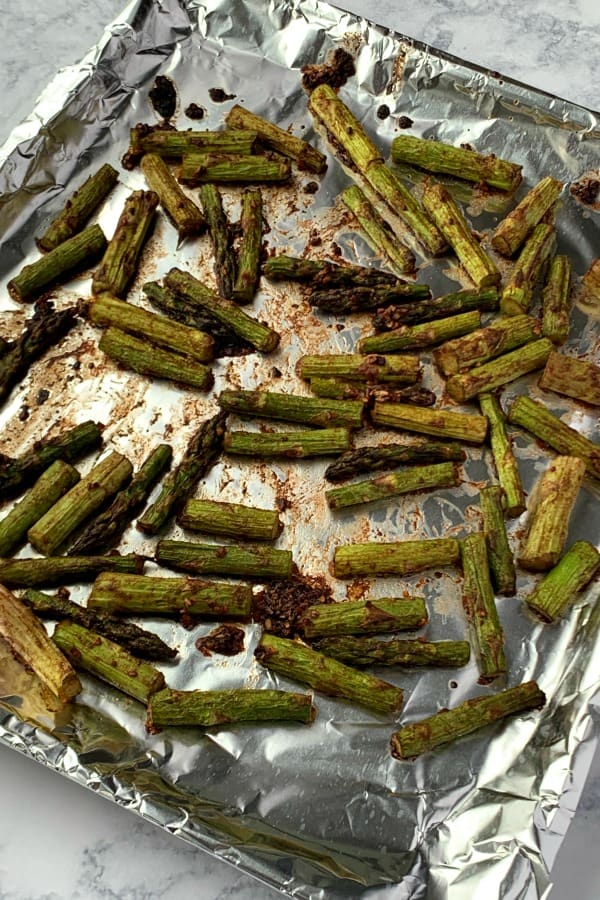 roasted asparagus on air fryer tray covered in foil