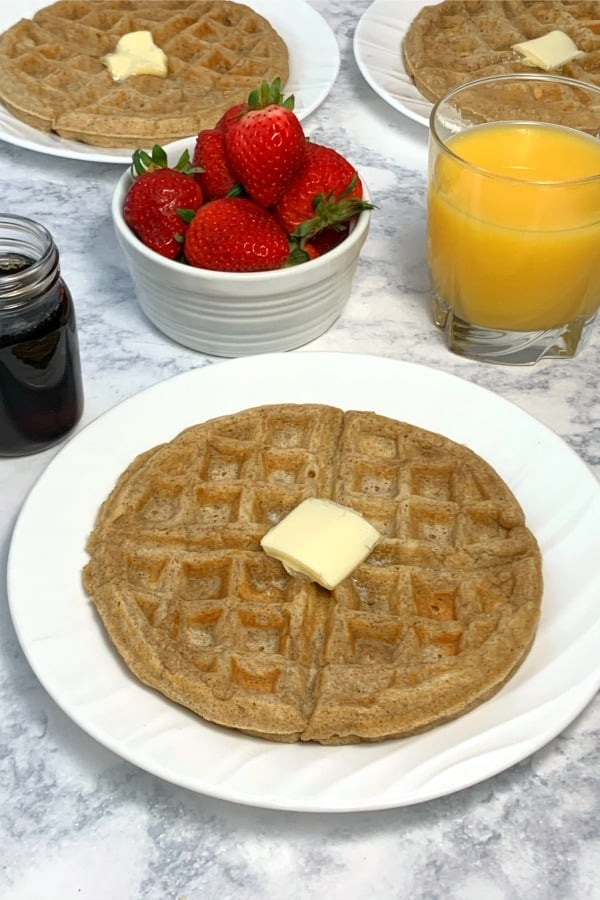 Oatmeal waffles on white plates with syrup, strawberries and orange juice