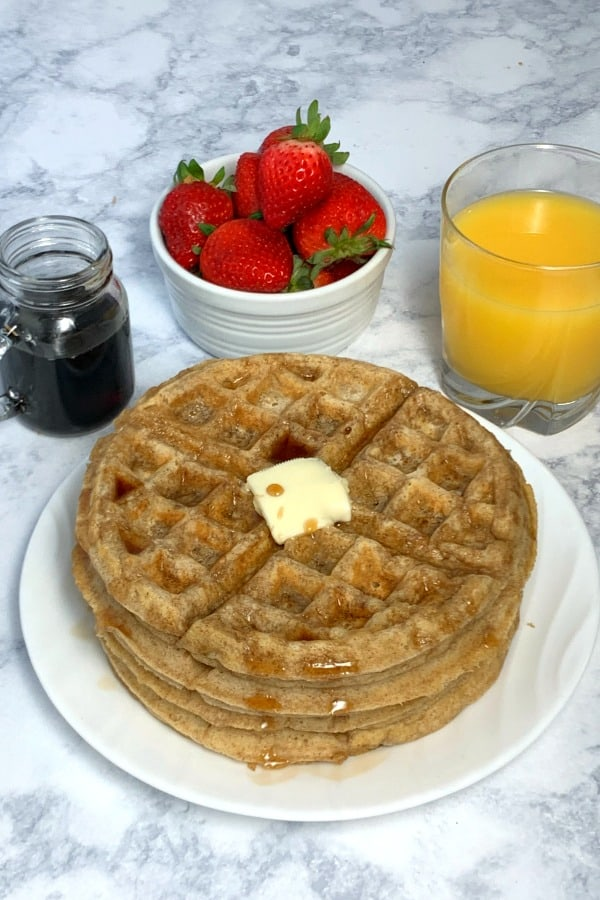 Oatmeal waffles on marble countertop with fruit, juice and syrup