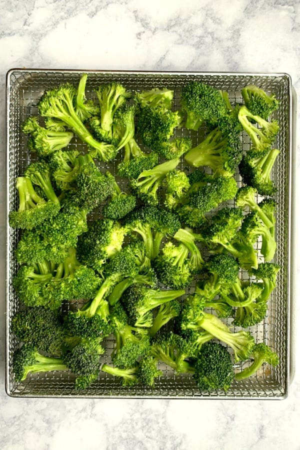 Air fryer basket of fresh broccoli