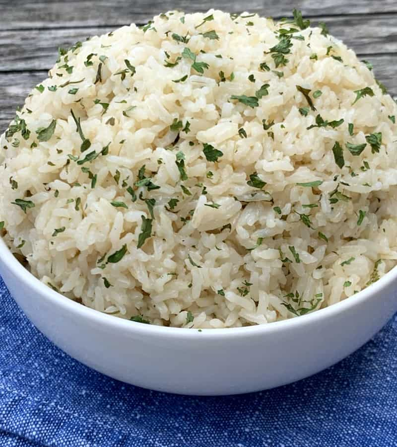 Side shot of Instant Pot rice pilaf in bowl with parsley and blue napkin on wood