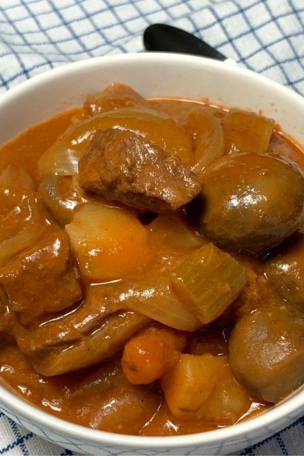 White bowl of farmhouse beef stew with healthy tomato base