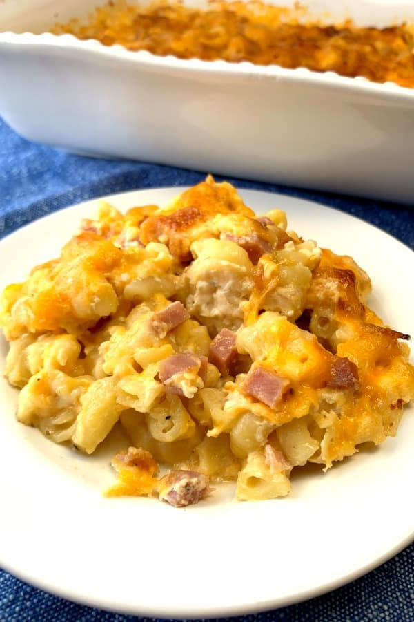 Leftover ham stirred into macaroni and cheese on a white plate