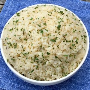 White bowl of rice pilaf on blue napkin