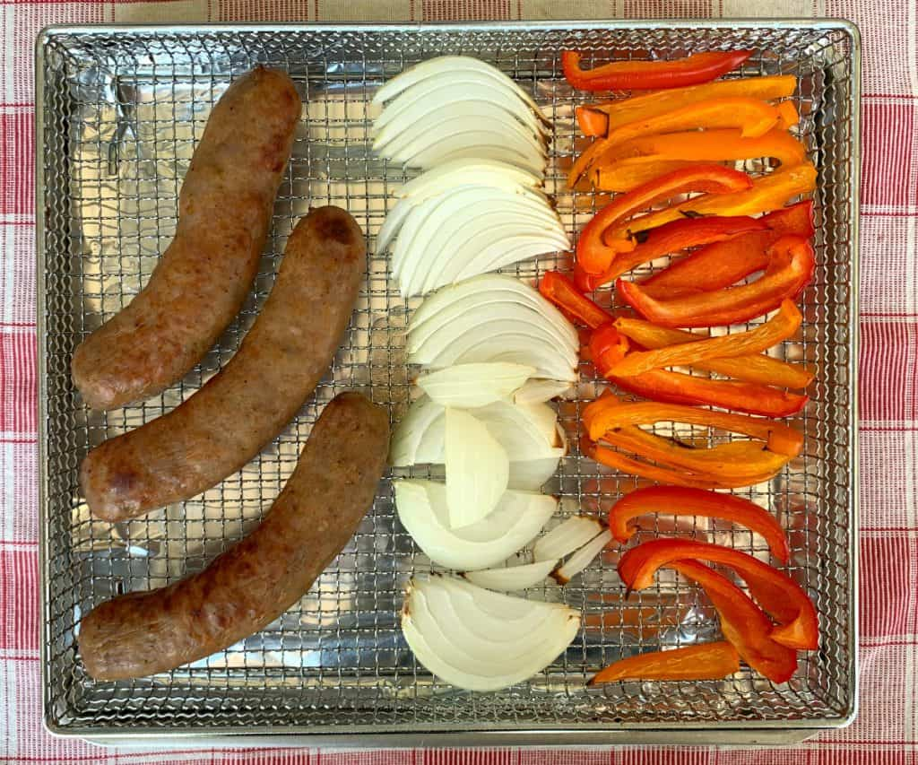 Air fryer basket with cooked Italian sausage, sweet onions and red and orange bell peppers