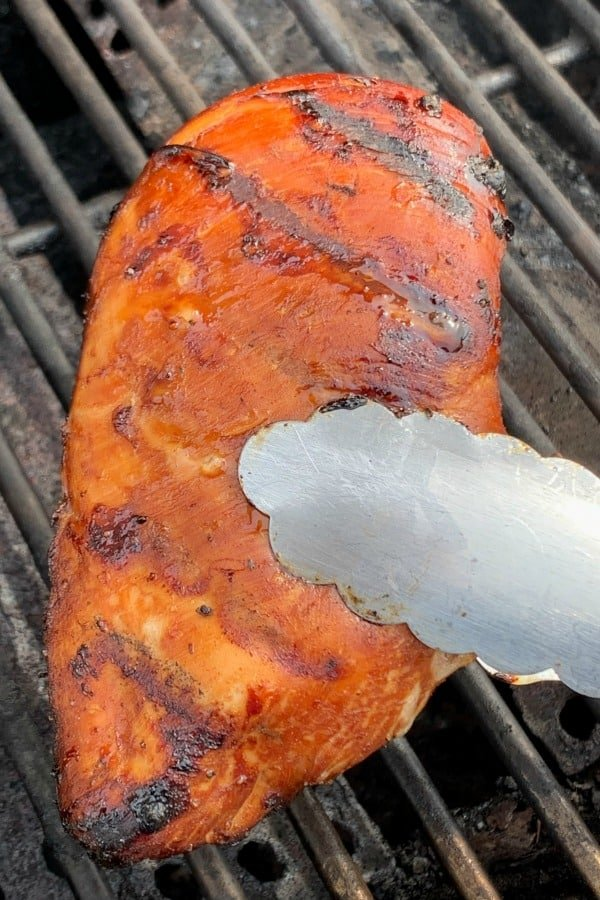 Chicken breast being held in tongs above a gas grill