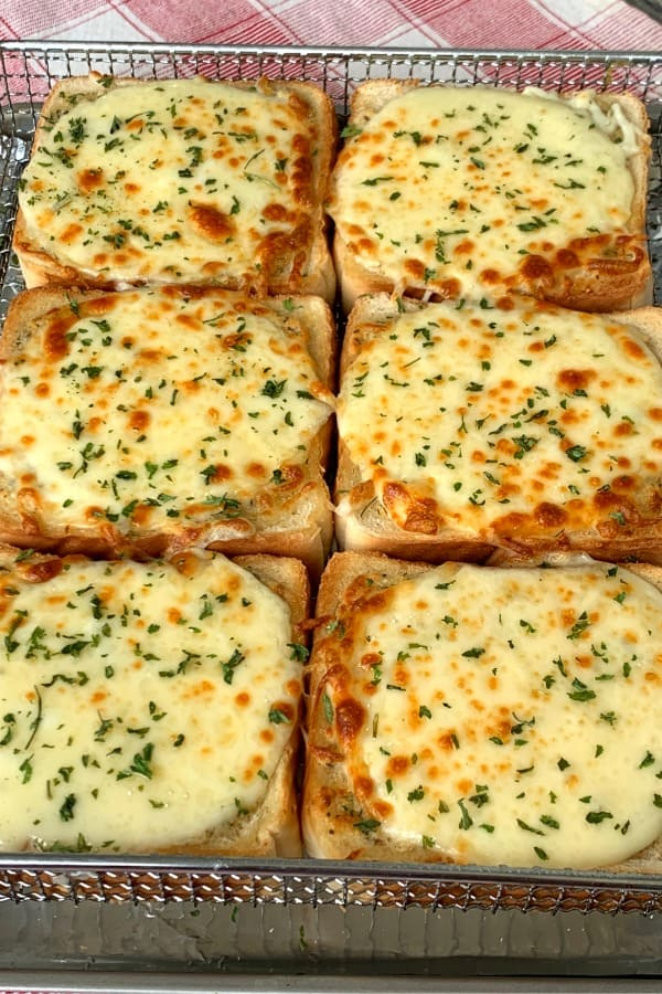 Homemade Cheesy Garlic Toast in air fryer tray on red plaid napkin
