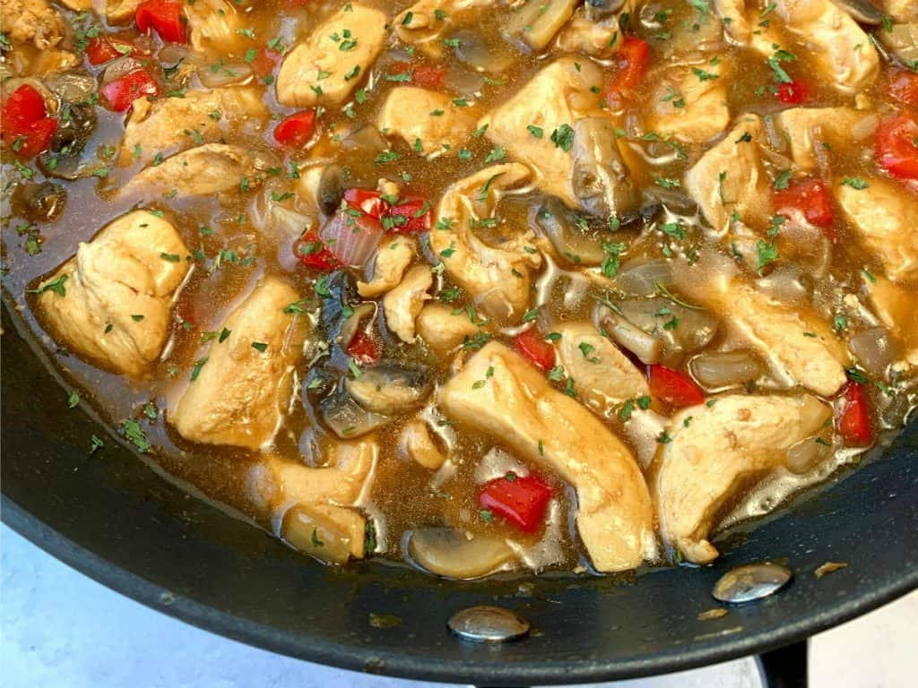 Chicken, pepper and mushrooms in brown sauce in a skillet