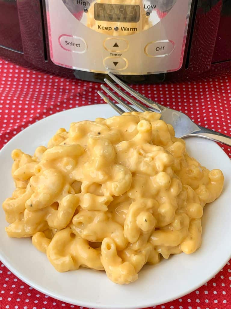 Super easy white plate of crock pot mac and cheese with a fork on a red napkin next to crock pot