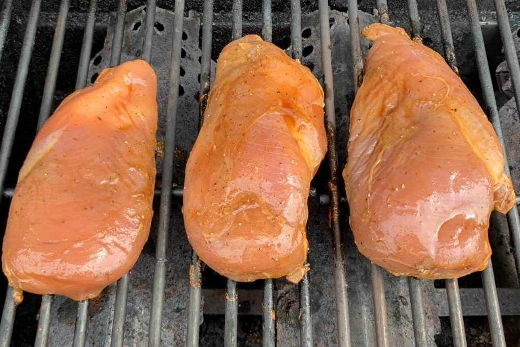 Marinated boneless, skinless chicken breasts on gas grill