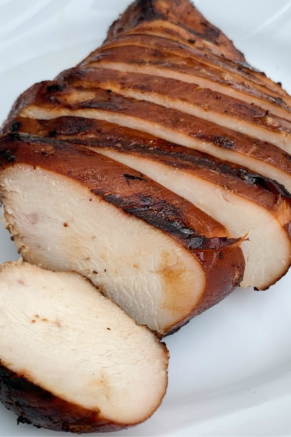 Marinated and grilled chicken breast sliced and sitting on a white plate