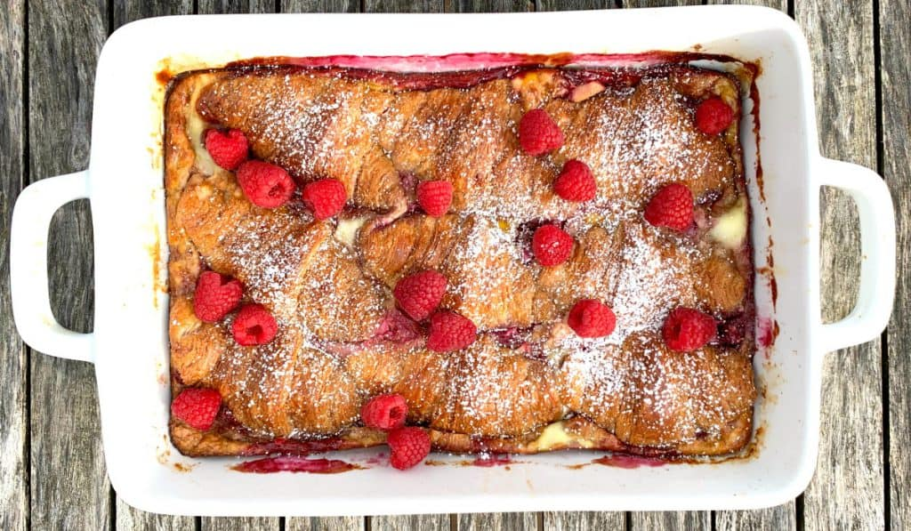 White 9x13 pan of raspberry croissant bake with powdered sugar and fresh raspberries