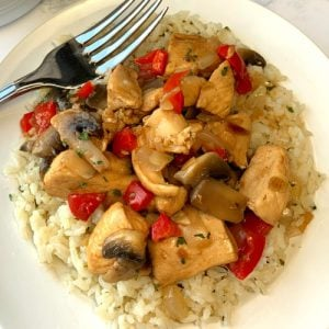 White plate with chicken and vegetables over rice with a fork