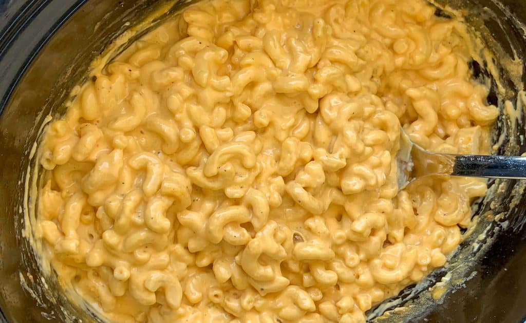 Crock pot full of easy macaroni and cheese with Velveeta on a serving spoon
