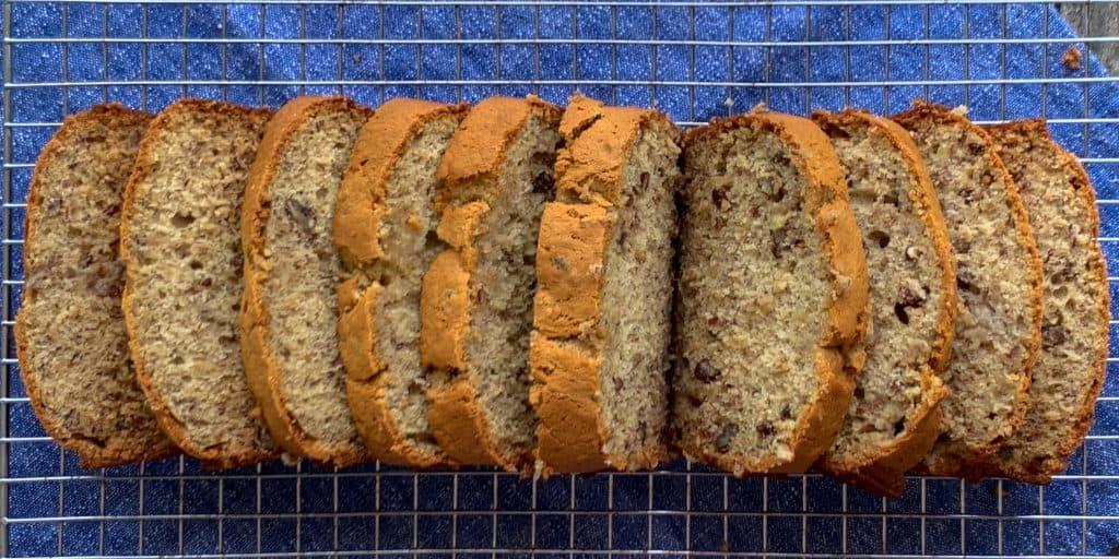 Loaf of sliced moist banana pecan bread on baking rack