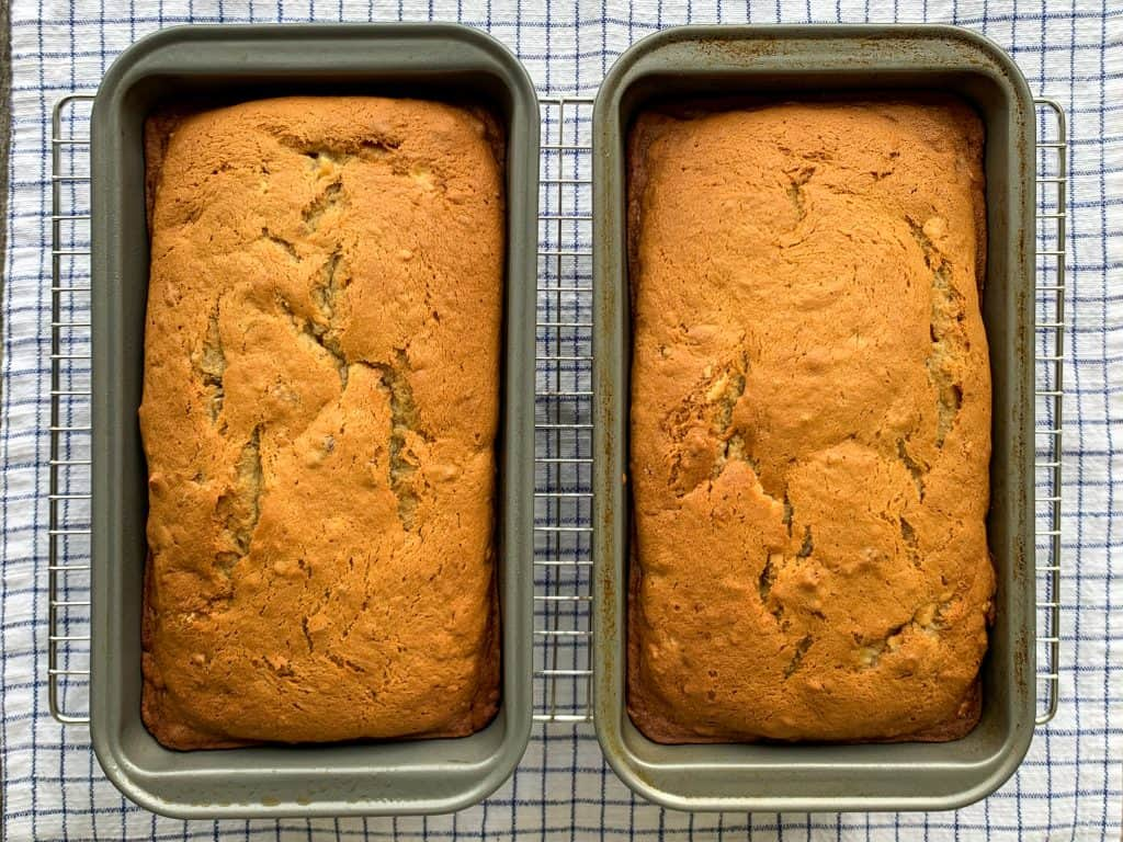 Two loaves of banana pecan bread in loaf pans on baking rack