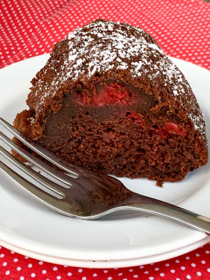 Piece of chocolate bundt cake with cherries on a white plate with a fork