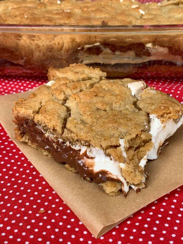 Piece of easy s'mores cake on brown parchment paper on red polka dot napkin