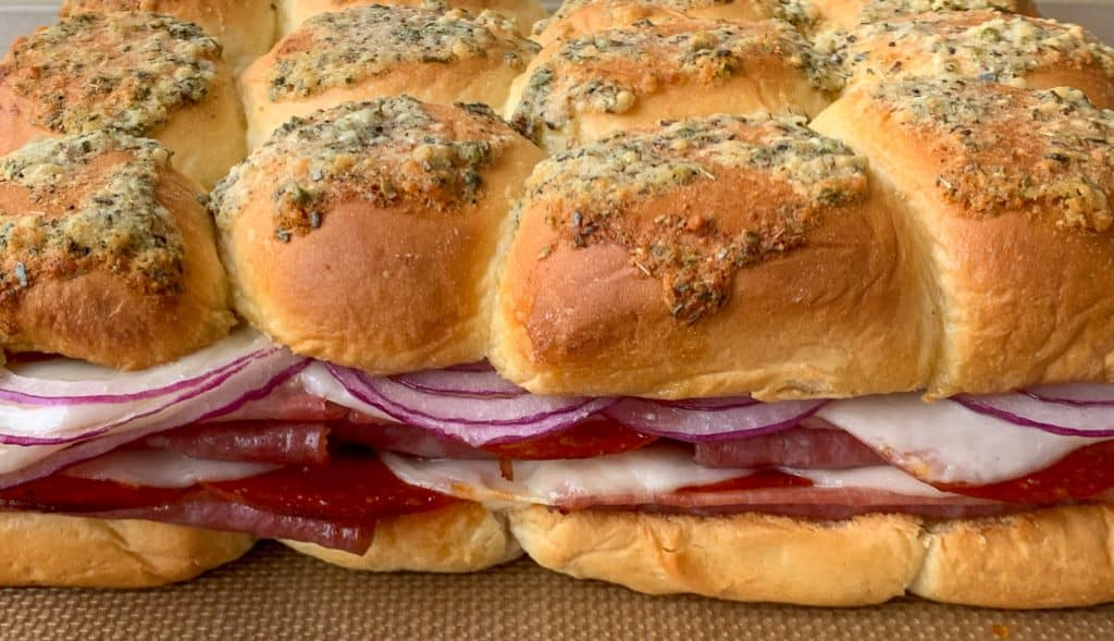 Oven baked Italian sliders with ham, salami, pepperoni, cheese and sliced red onions