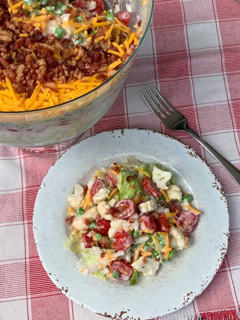 Layered overnight salad with mayonnaise on a plate and red plaid napkin next to serving dish