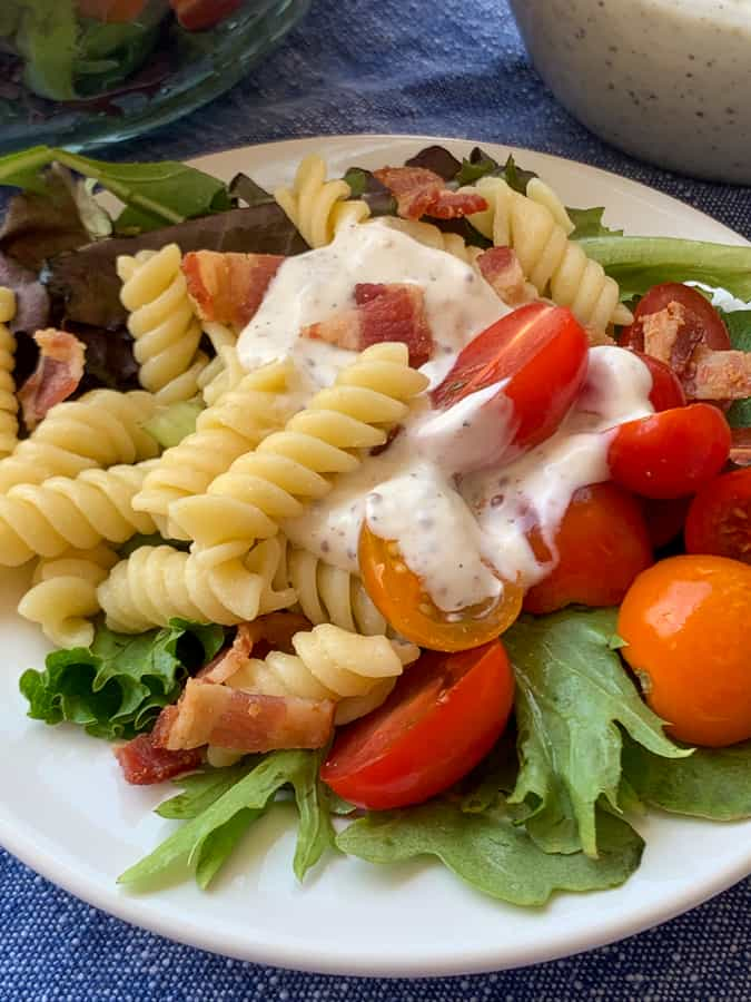 Homemade mayo and sour cream dressing on pasta salad on white plate