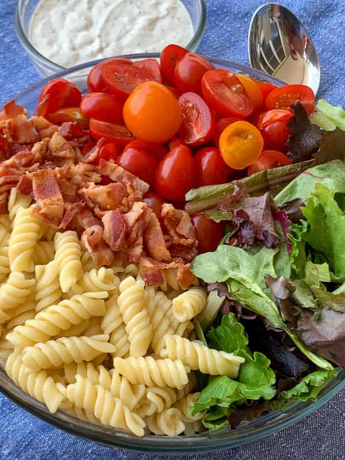 Homemade pasta salad dressing next to bowl of rotini pasta salad ingredients