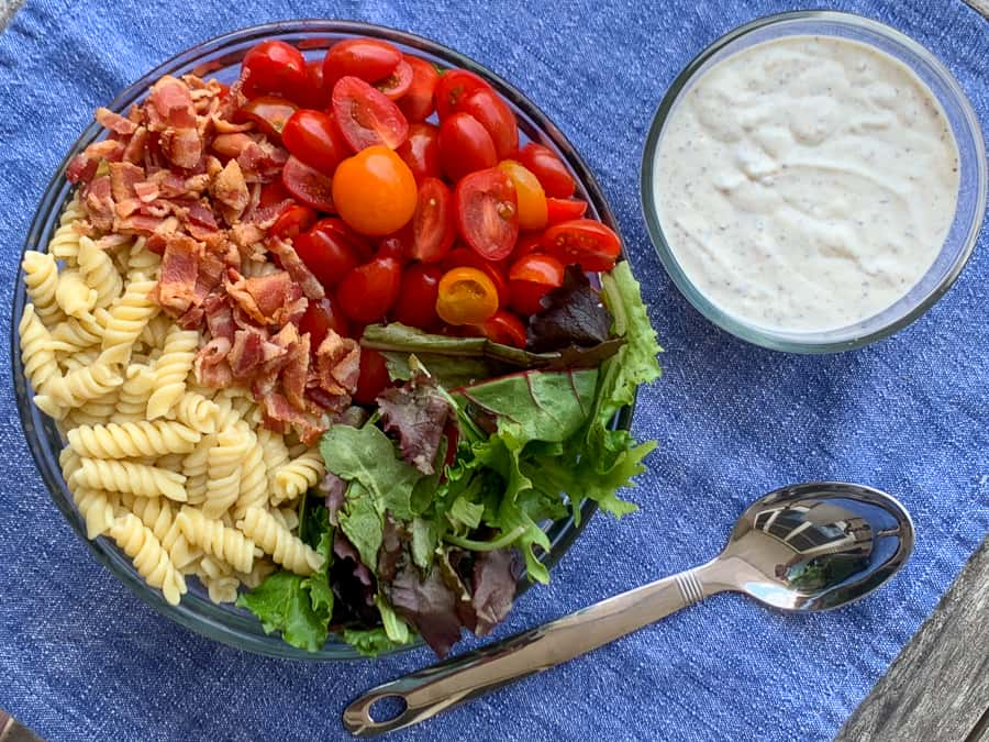 Summer's best pasta salad in glass bowl next to homemade dressing on blue napkin