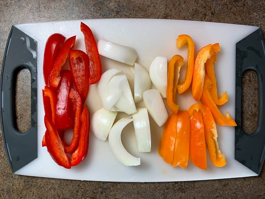 Thickly cut red and orange peppers and onions on a cutting board