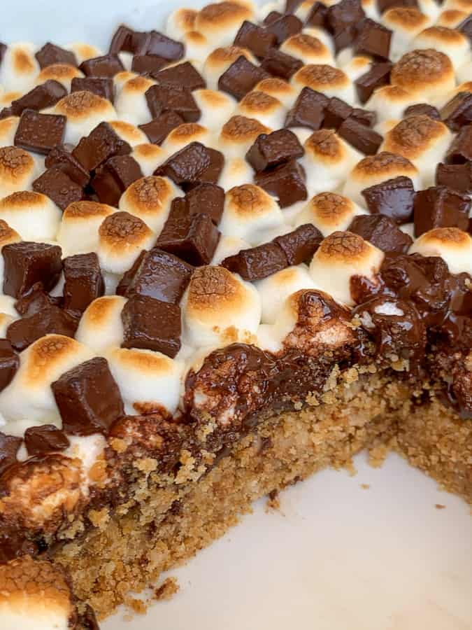 Smores bars in pan with a piece out showing thick graham cracker crust with chocolate layer and toasted marshmallows