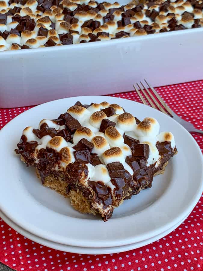 Piece of s'mores bars on a white plate by the 9 x 13 dish